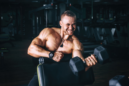 very power athletic guy bodybuilder , execute exercise with dumbbells, in dark gym Фото со стока