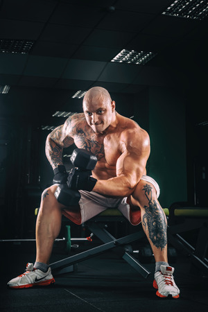 musculation: very power athletic guy bodybuilder , execute exercise with dumbbells, in dark gym Stock Photo