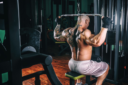 musculation: very power athletic guy bodybuilder, execute exercise with gym apparatus, on broadest muscle of back Stock Photo