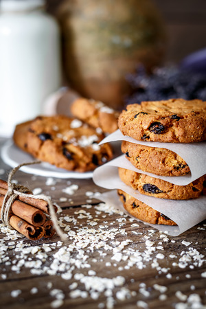 Homemade oatmeal cookies with nuts and raisins and glass of milk on dark wooden background