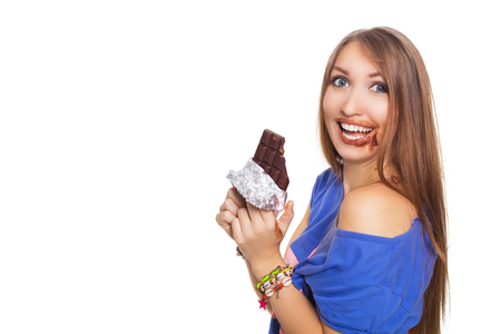 pretty woman eating chocolate with two hands, with some in her mouth. Isolatet on white. Stock Photo