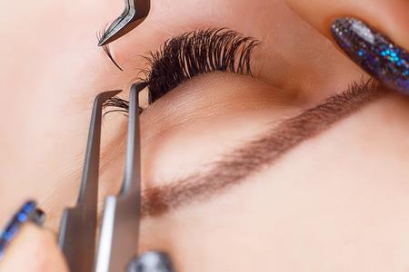 Wimper Extension Procedure. Vrouw oog met lange wimpers. Lashes, close-up, macro, selectieve aandacht. Stockfoto
