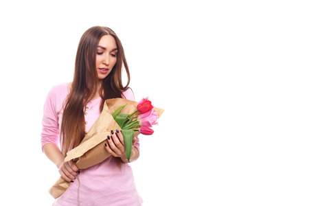Beautiful girl in the pink dress with flowers tulips in hands on a white background. Isolated on white.