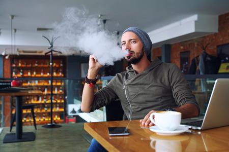 Young handsome hipster man with beard sitting in cafe with a cup of coffee, vaping and releases a cloud of vapor. Working at laptop and having a little break. With copy space. Foto de archivo
