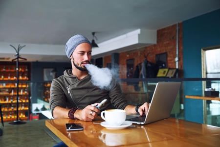 Young handsome hipster man with beard sitting in cafe with a cup of coffee, vaping and releases a cloud of vapor. Working at laptop and having a little break. With copy space. 写真素材