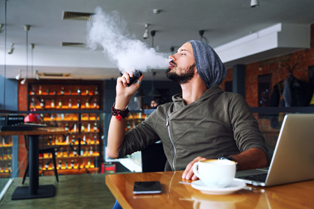 Young handsome hipster man with beard sitting in cafe with a cup of coffee, vaping and releases a cloud of vapor. Working at laptop and having a little break. With copy space. 免版税图像