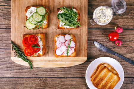 Four sandwiches with fresh vegetables, tomatoes, cucumbers, radish and arugula on a wooden background. Homemade butter and toast. Top view. Stock Photo