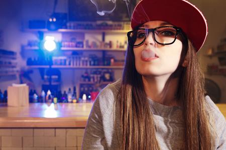 Young pretty woman in red cap smoke an electronic cigarette at the vape shop. Closeup.