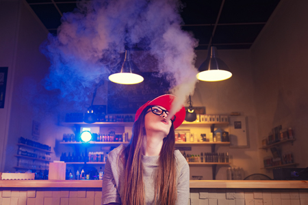 Young pretty woman in red cap smoke an electronic cigarette at the vape shop 免版税图像 - 76416965