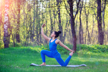 veda: Young woman doing yoga exercises in the summer city park. Health lifestyle concept. Stock Photo