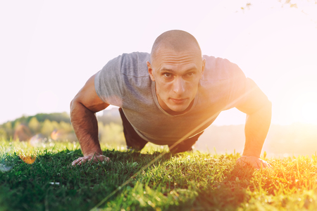 Athlete doing squeezing at sunset in the park Stock Photo