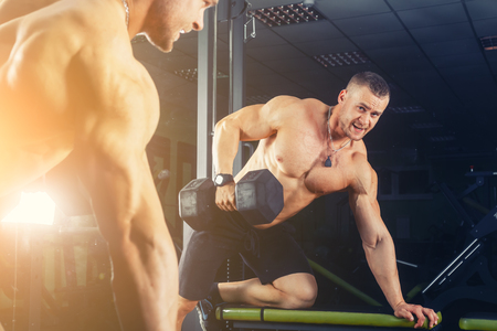 musculation: power athletic guy , execute exercise press with dumbbells, in sport hall Stock Photo