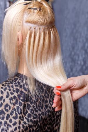 Hair extensions procedure. De kapper doet haaruitbreidingen aan jong meisje, blonde in een schoonheidssalon. Selectieve aandacht. Stockfoto