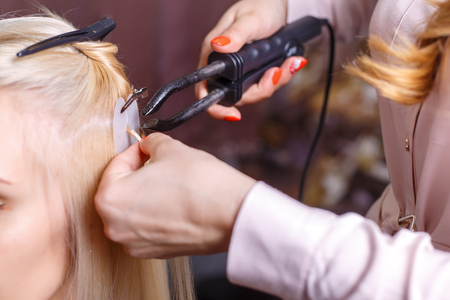 Hair extensions procedure hairdresser does hair extensions to hair extensions procedure hairdresser does hair extensions to young girl blonde in a beauty pmusecretfo Image collections