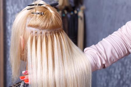 Haarverlängerungsverfahren. Friseur macht Haarverlängerungen zum jungen Mädchen, Blondine in einem Schönheitssalon. Selektiver Fokus