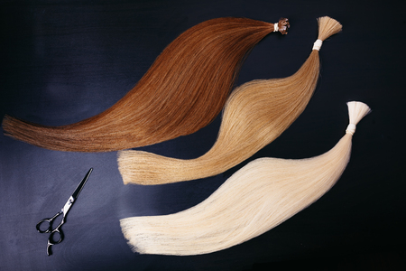 hair extensions of three colors on a dark background with scissors. copyspace. top view.
