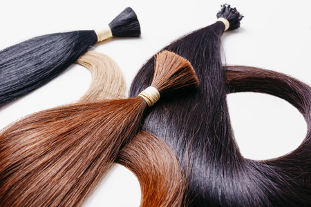 hair extensions of three colors on a white background. copyspace selective focus Stock Photo