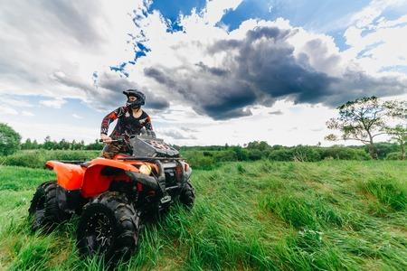 VITEBSK, BELARUS - JUNE 11, 2017: Photo of man on the ATV Quad Bike running in field Editorial