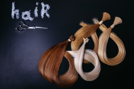 hair extensions of three colors on a dark background. copyspace. top view.