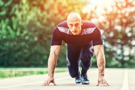 Bald Athletic Man in Running Start Posizione e guardando alla distanza in stadio.