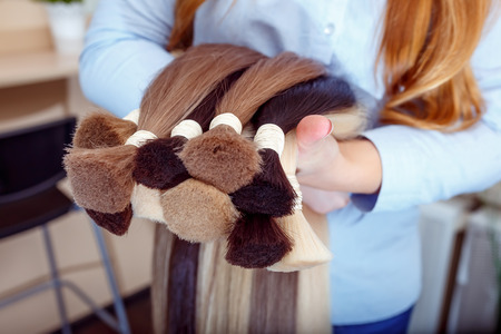 Woman holds hair extension equipment of natural hair. hair samples of different colors