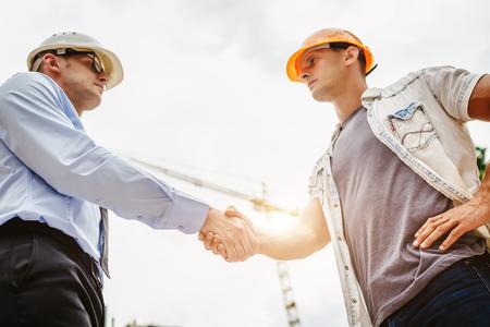 Architecten ingenieur schudt andere handen op bouwplaats. Business teamwork, samenwerking, succes samenwerking concept