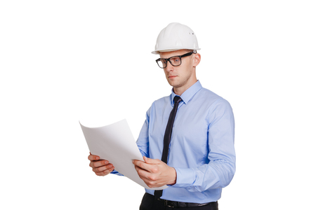 Construction engineer looking at the blueprint. Isolated on white.