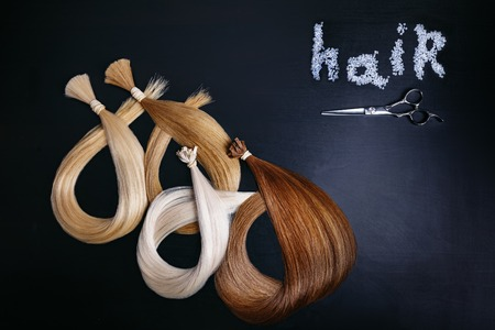 hair extensions of four colors on a dark background with scissors. copyspace. top view.