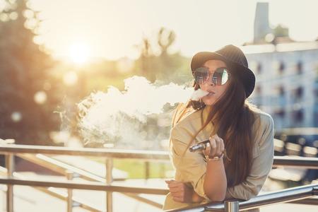 Vrij jonge hipstervrouw in zwarte hoed vape ecig, vaping apparaat bij de zonsondergang. Getinte afbeelding.