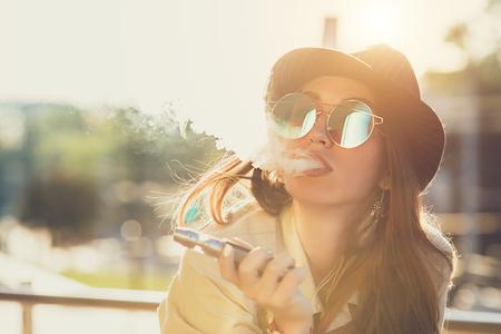 Pretty young hipster woman in black hat vape ecig, dispositif de vaping au coucher de soleil. Image tonifiée. Banque d'images - 84416943
