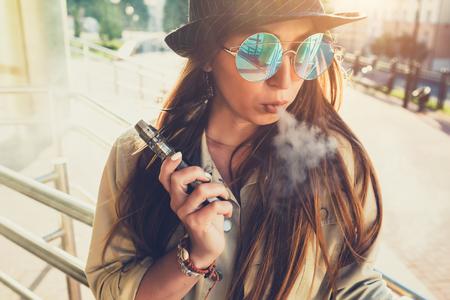 Pretty young hipster woman in black hat vape ecig, dispositif de vaping au coucher de soleil. Image tonifiée. Banque d'images - 84416944