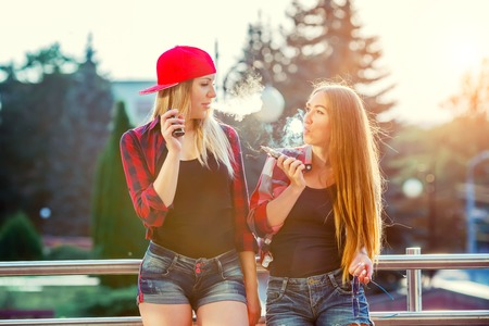 Two women vaping outdoor. The evening sunset over the city. Toned image. Archivio Fotografico