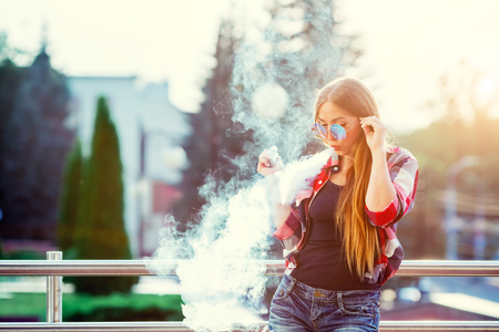Young pretty hipster woman vaping and releases a cloud of vapor. The evening sunset over the city. Toned image.