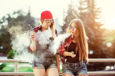 Two women vaping outdoor. The evening sunset over the city. Toned image. 免版税图像