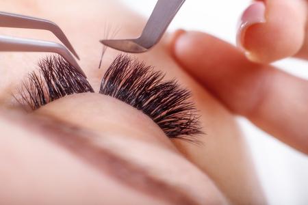 Eyelash Extension Procedure. Woman Eye with Long Eyelashes. Lashes, close up, macro, selective focus.