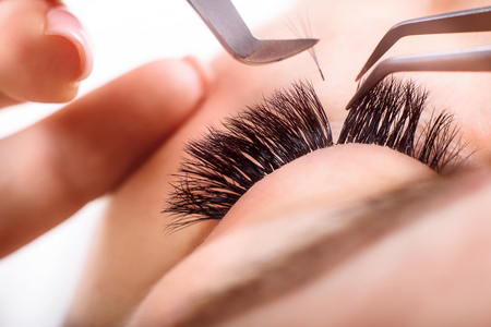 Wimper Extension Procedure. Vrouw oog met lange wimpers. Lashes, close-up, macro, selectieve aandacht. Stockfoto