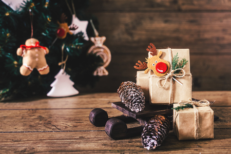 Christmas Gifts with Boxes on Wooden Background. Vintage Style. Closeup, selective focus. Toy, bear, sled. Christmas concept.