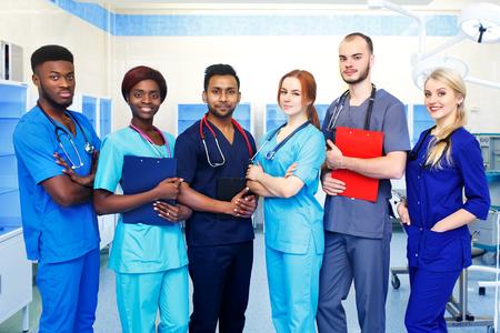 Squadra multirazziale di giovani medici in un ospedale in piedi in una sala operatoria