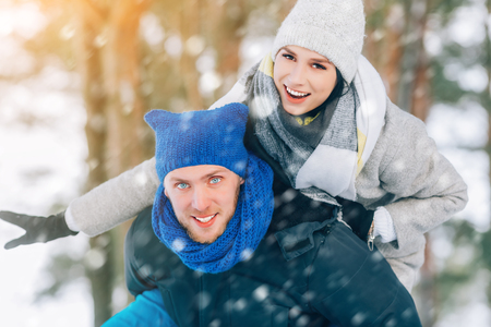 Happy Young Couple in Winter Park laughing and having fun. Family Outdoors.