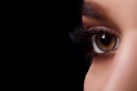 Eyelash Extension Procedure. Woman Eye with Long Eyelashes after Extension Procedure. White eyelashes. Dark background. Makeup. Close up, selective focus. Stock Photo