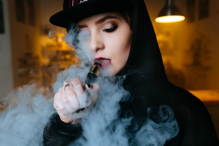 Vaping girl. Young hipster woman vape e-cig at the vapeshop. Hip-hop style. Closeup.