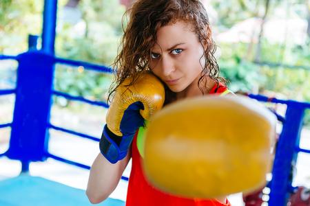 female boxer inside thai boxing ring. angree emotions.