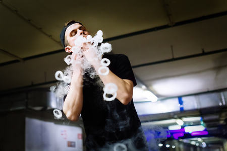 Man in cap smoke an electronic cigarette and releases clouds of vapor performing various kind of vaping tricks