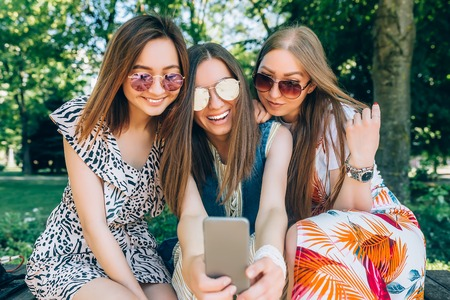 Happy friends in the park on a sunny day . Summer lifestyle portrait of three multiracial women enjoy nice day, wearing bright sunglasses. Taking picture on mobile phone. Best friends girls having fun, joy. Lifestyle