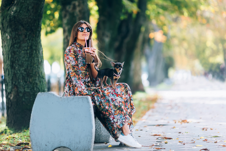 Young woman in sunglasses with milkshake. Outdoor lifestyle portrait of pretty smiling female with little puppy in autumn park