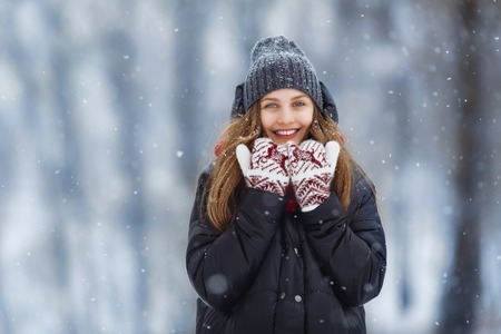 Winter young woman portrait. Beauty Joyful Model Girl laughing and having fun in winter park. Beautiful young female outdoors, Enjoying nature, wintertime Stock fotó