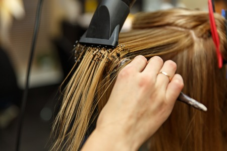 Professional hairdresser dyeing hair of her client in salon. Haircutter dry hair with hairdrier. Selective focus.
