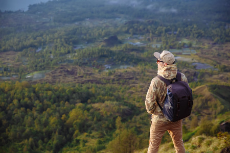 Man tourist looks at the sunrise on the volcano Batur on the island of Blai in Indonesia. Hiker man with backpack travel on top mountain, travel concept