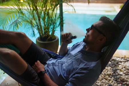 Man resting in a hammock and vaping and letting off steam from an electronic cigarette Stok Fotoğraf