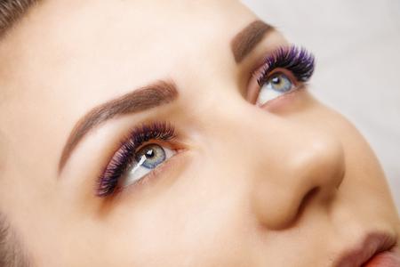 Wimpernverlängerungsverfahren. Frauenauge mit langen blauen Wimpern. Ombre-Effekt. Nahaufnahme, selektiver Fokus. Standard-Bild